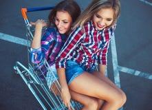 Twee gelukkige mooie tienermeisjes die boodschappenwagentje in openlucht drijven Royalty-vrije Stock Foto's