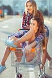 Twee gelukkige mooie tienermeisjes die boodschappenwagentje in openlucht drijven Stock Afbeeldingen