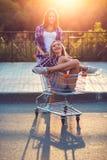 Twee gelukkige mooie tienermeisjes die boodschappenwagentje in openlucht drijven Royalty-vrije Stock Afbeelding