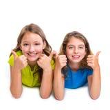 Twee gelukkige o.k. duimen van jong geitjemeisjes op gebaar het liggen royalty-vrije stock afbeelding