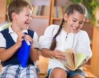 Twee gelukkige schoolkinderen hebben pret in klaslokaal Stock Afbeeldingen