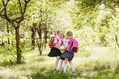 Twee gelukkige schoolmeisjes van primaire klassen in openlucht stock foto's