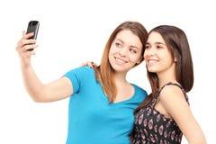 Twee gelukkige tieners die beelden van zich met een celtelefoon nemen Royalty-vrije Stock Afbeeldingen