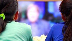 Twee gelukkige tieners die op nieuws op slimme TV letten stock footage