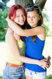 Twee gelukkige vrienden die van yungvrouwen roddel en het lachen delen Stock Fotografie