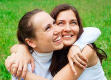 Twee gelukkige vrienden omhelst Stock Foto's