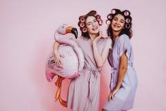 Twee Gelukkige Vrouwen in Badjassen op Roze Achtergrond stock afbeeldingen