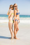 Twee gelukkige vrouwen in bikini en zonnebril die zich rijtjes bevinden Stock Foto's