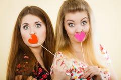 Twee gelukkige vrouwen die hart op stok houden royalty-vrije stock fotografie