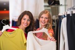 Twee gelukkige vrouwen die in klerenopslag winkelen stock afbeelding