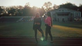 Twee gelukkige vrouwen die plantaardige smoothie na geschiktheids lopende training drinken op stadion Geschiktheid en gezonde lev stock video