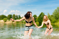 Twee gelukkige vrouwen die pret hebben bij meer in de zomer Royalty-vrije Stock Fotografie