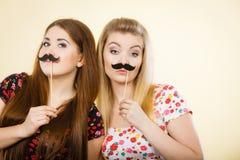 Twee gelukkige vrouwen die valse snor op stok houden stock afbeeldingen