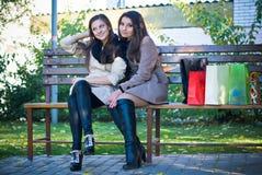 Twee Gelukkige Vrouwen, meisjes die na het winkelen reis rusten Royalty-vrije Stock Foto's