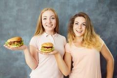 Twee gelukkige vrouwen met heerlijke hamburgers in handen royalty-vrije stock fotografie