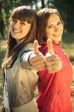 Twee gelukkige vrouwen met omhoog duimen Royalty-vrije Stock Foto