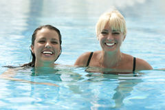 Twee gelukkige vrouwen in pool stock foto's