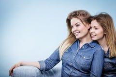 Twee gelukkige vrouwenvrienden die jeansuitrusting dragen Stock Foto