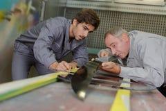 Twee gelukkige werklieden die op slotenmakersworkshop hard werken stock fotografie