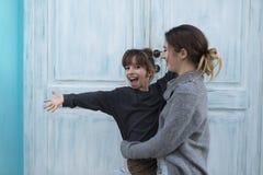 Twee gelukkige zusters naast een blauw Stock Afbeeldingen