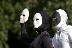 Twee gemaskeerde actoren die zwart-witte kostuums dragen Stock Fotografie