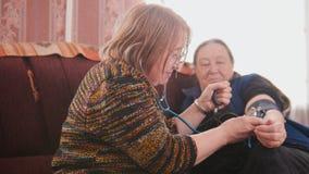 Twee gepensioneerden - hogere dames die gezondheidszorgstaat met manometer controleren - maatregelendruk, bejaarde levensstijl royalty-vrije stock afbeeldingen