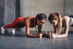Twee geschikte vrouwen die de Fitness van de plankoefening sporttraining doen stock afbeeldingen