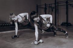 Twee geschikte vrouwen die in gymnastiek geschiktheidsoefeningen met domoren doen die in plank blijven stellen, zwart-wit Stock Afbeeldingen