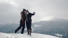 Twee girlfriends do selfie bij bergbovenkant stock footage
