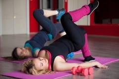 Twee girls do aerobics oefeningen op matten in geschiktheidscentrum Stock Afbeeldingen