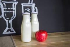 Twee glas witte flessen en een verse appel op de lijst stock afbeeldingen