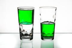 Twee glazen, beide halfvol van groene vloeistof Stock Afbeeldingen