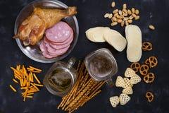 Twee glazen bier en snacks, een worstplaat en een gerookte kip thighson een concrete zwarte lijst Royalty-vrije Stock Foto