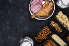 Twee glazen bier en snacks, een worstplaat en een gerookte kip thighson een concrete zwarte lijst Royalty-vrije Stock Afbeeldingen