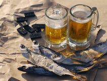 Twee glazen bier, zoute vissen en beenderen van domino's Royalty-vrije Stock Afbeelding