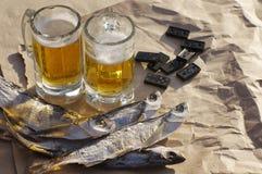 Twee glazen bier, zoute vissen en beenderen van domino's Stock Afbeeldingen