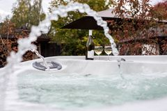Twee glazen champagne dichtbij openluchtjacuzzi Romantische Ontsnapping De achtergrond van valentijnskaarten Horizontale, ondiepe royalty-vrije stock afbeeldingen