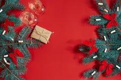 Twee glazen champagne met Kerstboom vertakken zich en kleine gift op een rode achtergrond Stock Afbeelding