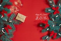 Twee glazen champagne met Kerstboom vertakken zich en kleine gift op een rode achtergrond Royalty-vrije Stock Afbeeldingen