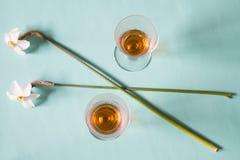 Twee glazen cognac of brandewijn en witte gele narcissen op neutral Royalty-vrije Stock Afbeeldingen
