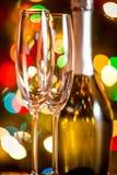 Twee glazen en fles champagne tegen het fonkelen Kerstmis Stock Foto