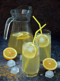 Twee glazen en karaf koude eigengemaakte limonade met citroenplakken, ijsblokjes, bruine suiker, geel stro Stock Foto's