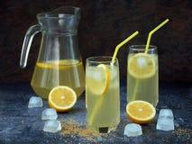 Twee glazen en karaf koude eigengemaakte limonade met citroenplakken, ijsblokjes, bruine suiker, geel stro Stock Afbeeldingen
