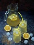 Twee glazen en kruik koude eigengemaakte limonade met citroenplakken, ijsblokjes, bruine suiker, geel stro Royalty-vrije Stock Afbeeldingen