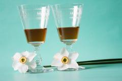 Twee glazen fles cognac of brandewijn en witte gele narcissen  Royalty-vrije Stock Afbeeldingen