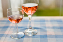 Twee Glazen half Volledige Rode Rose Wine Blue Checked Table Horizonta Royalty-vrije Stock Afbeelding