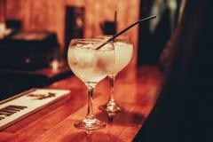 Twee glazen jenever en tonicum met ijs en stro in barteller royalty-vrije stock afbeelding