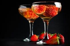 Twee glazen koude champagne met aardbeien stock afbeeldingen