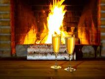 Twee glazen met champagne op een houten lijst dichtbij de open haard met het branden van berkehout royalty-vrije stock foto's