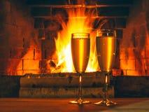 Twee glazen met champagne op een houten lijst dichtbij de open haard met het branden van berkehout stock afbeelding